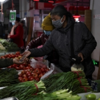 Customers shop for vegetable at a market in Shenyang, China, earlier this month. President Xi Jinping launched a high-profile campaign against food waste this summer, seeking to eliminate a deep-rooted custom of ordering excessive dishes in restaurants as a demonstration of wealth and generosity. | AFP-JIJI
