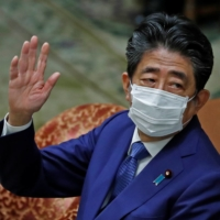 Former Prime Minister Shinzo Abe gestures while attending a session of the Diet's Lower House in Tokyo on Friday to face questioning over a possible violation of election funding laws. | REUTERS