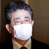 Former Prime Minister Shinzo Abe arrives at the Diet building in Tokyo on Friday to face questions over a possible violation of election funding laws. | REUTERS