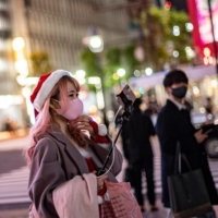 A woman wearing a Santa hat films in the Shibuya district of Tokyo on Thursday. | AFP-JIJI