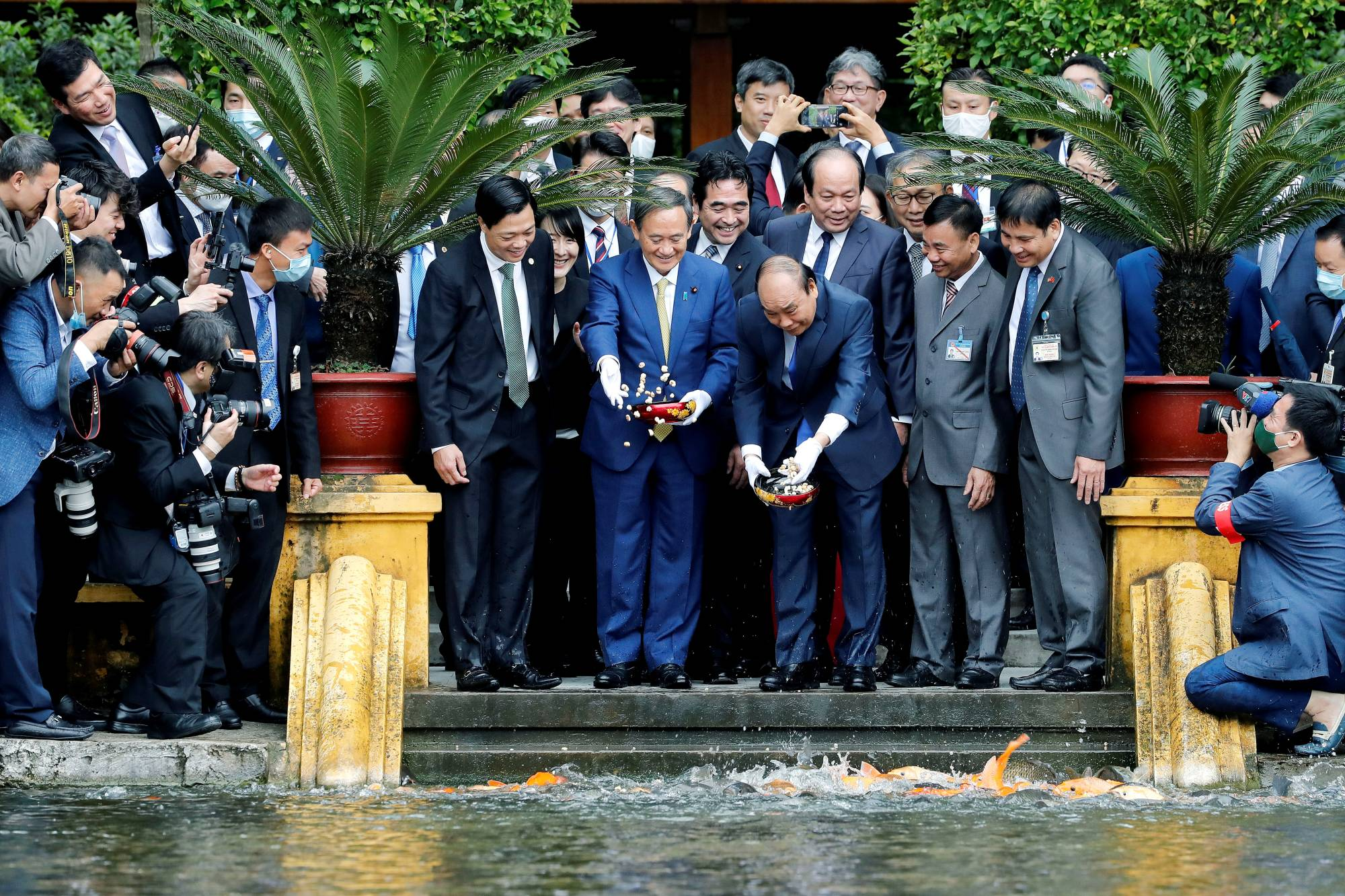 Prime Minister Yoshihide Suga and his Vietnamese counterpart, Nguyen Xuan Phuc, feed the fish by a pond at the Presidential Palace compound in Hanoi in October. | POOL / VIA REUTERS