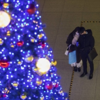 A man and a woman both wearing face masks take a photo of a Christmas tree display in Tokyo on Friday. | AP