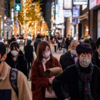 People walk in a shopping area on Christmas Eve in the Ginza district of Tokyo. | AFP-JIJI