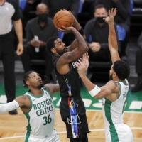 Nets guard Kyrie Irving shoots while being defended by the Celtics' Marcus Smart (left) and Jayson Tatum in Boston on Friday. | AP