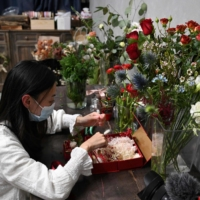 Florist Elise Ip makes a gift as part of the free Send Flowers With You project that allows relatives and friends to receive gifts from protesters who are behind bars.    AFP-JIJI