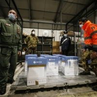 COVID-19 vaccines arrive at a military airport Saturday in Rome.  | LAPRESSE / VIA AP