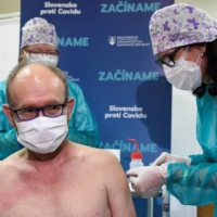 A medical professional receives an injection with a dose of the Pfizer-BioNTech COVID-19 vaccine at  University Hospital in Nitra, Slovakia, on Saturday. | REUTERS