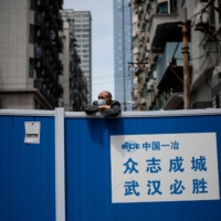 A man looks over a barricade set up to keep people out of a residential compound in Wuhan, China, in April.  | AFP-JIJI