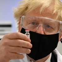 U.K. Prime Minister Boris Johnson poses with a vial of the AstraZeneca-Oxford University COVID-19 candidate vaccine at Wockhardt's pharmaceutical manufacturing facility in Wrexham, Wales, in November.  | POOL / VIA REUTERS