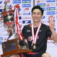 Kento Momota flashes a 'three' sign with his trophy after winning his third straight national badminton title on Sunday at Machida City Gymnasium in western Tokyo. | KYODO