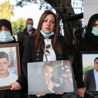 Samia Doughan (center) holds a picture of her husband, Mohammad, who was killed in the Aug. 4 explosion in Beirut, during a protest near the port on Dec. 4 marking four months since the blast.   | REUTERS