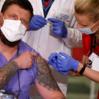 A paramedic is vaccinated with the Pfizer-BioNTech COVID-19 vaccine in Warsaw, Poland, on Sunday.  | REUTERS
