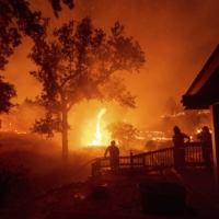 Firefighters watch flames from the LNU Lightning Complex fires approach a home in Napa County, California. Wildfires that scorched record areas in California, Australia and even Russia's Siberian hinterland are also consistent with a warmer world, and a predicted to get worse as temperatures climb. | AP