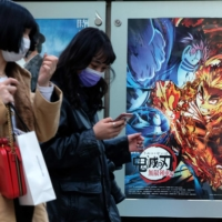 "Pedestrians walk past a poster promoting the anime film ""Demon Slayer: Kimetsu no Yaiba the Movie: Mugen Train"" at a cinema in Tokyo on Dec. 16. The movie became the highest-grossing film in Japanese box-office history on Monday."