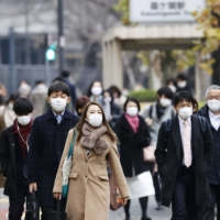 People walk to work Monday morning in the Kasumigaseki district of Tokyo. | KYODO