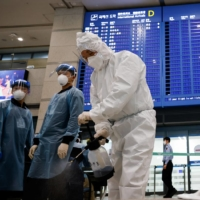 Workers disinfect an arrival gate at Incheon International Airport in Incheon, South Korea, on Monday.  | REUTERS
