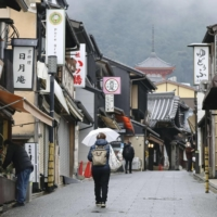 Few people are seen in the usually crowded street near Kiyomizu Temple in Kyoto on Monday, when the nationwide suspension of the Go To Travel program began. | KYODO