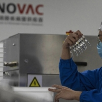 A worker inspects syringes of a vaccine for COVID-19 produced by Sinovac at its factory in Beijing in September. | AP