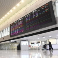 Almost no passengers can be seen in the arrivals lobby at Narita Airport on Monday. The government imposed new travel restrictions the same day. | KYODO