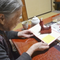 Setsuko Miyazawa, grandmother of Niina Miyazawa who was killed 20 years ago along with her family, looks at a card sent from Niina's former classmate earlier this month in the city of Saitama. | KYODO