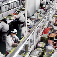 People work in a factory in China's Shaanxi Province in March. Nearly half of 96 major Japanese companies which responded to a survey said they are diversifying their supply chains to reduce reliance on China. | XINHUA NEWS AGENCY / VIA KYODO