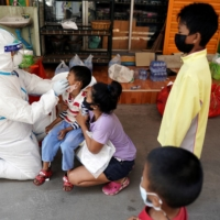 A health care worker takes a nasal swab sample of a child for a COVID-19 test at a migrant community in Samut Sakhon province, Thailand, on Dec. 20.   | REUTERS