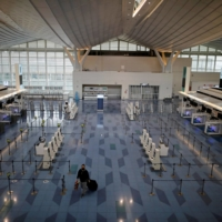 An almost empty check-in area of the international flight terminal of Haneda Airport on Monday. | REUTERS