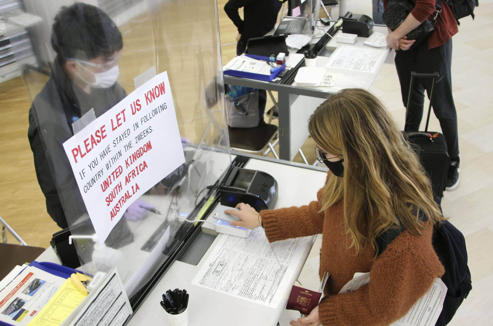 A passenger arriving from the Netherlands at Narita International Airport on Monday holds her mobile phone over a device to submit answers to a questionnaire on health conditions and travel history. | KYODO