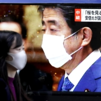 A large screen in Tokyo's Yurakucho district shows news about former Prime Minister Shinzo Abe taking questions in a Lower House session on Friday. | KYODO