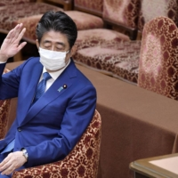 Former Prime Minister Shinzo Abe reacts during a Lower House session on Friday. | KYODO