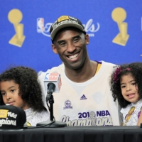 Lakers guard Kobe Bryant speaks during a news conference with his daughters Gianna (right) and Natalia after Game 7 of the 2010 NBA Finals in Los Angeles on June 17, 2010. | USA TODAY / VIA REUTERS