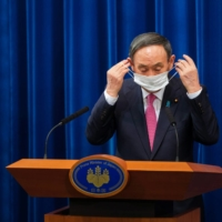 Japanese Prime Minister Suga Yoshihide puts a protective face mask on after a news conference about the coronavirus pandemic, in Tokyo on Dec. 25. | POOL VIA / REUTERS