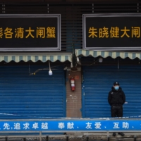 A security guard stands outside the Huanan Seafood Wholesale Market in January. | AFP-JIJI