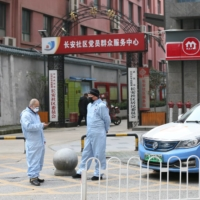 Taxi drivers use protective suits in front of a residential area of Wuhan in January.  | CHINA DAILY / VIA REUTERS
