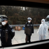 A medical worker and police wait for drivers at a checkpoint in Yunxi county, in China's Hunan province, near the border to Hubei province, amid lockdowns in January.   | REUTERS