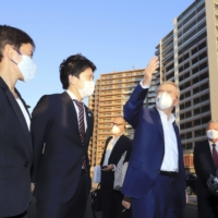 Saburo Kawabuchi (right), mayor of the Olympic village, accompanies IOC chairman Thomas Bach (center) during his visit to the Olympic village in Tokyo's Chuo Ward in November. | KYODO
