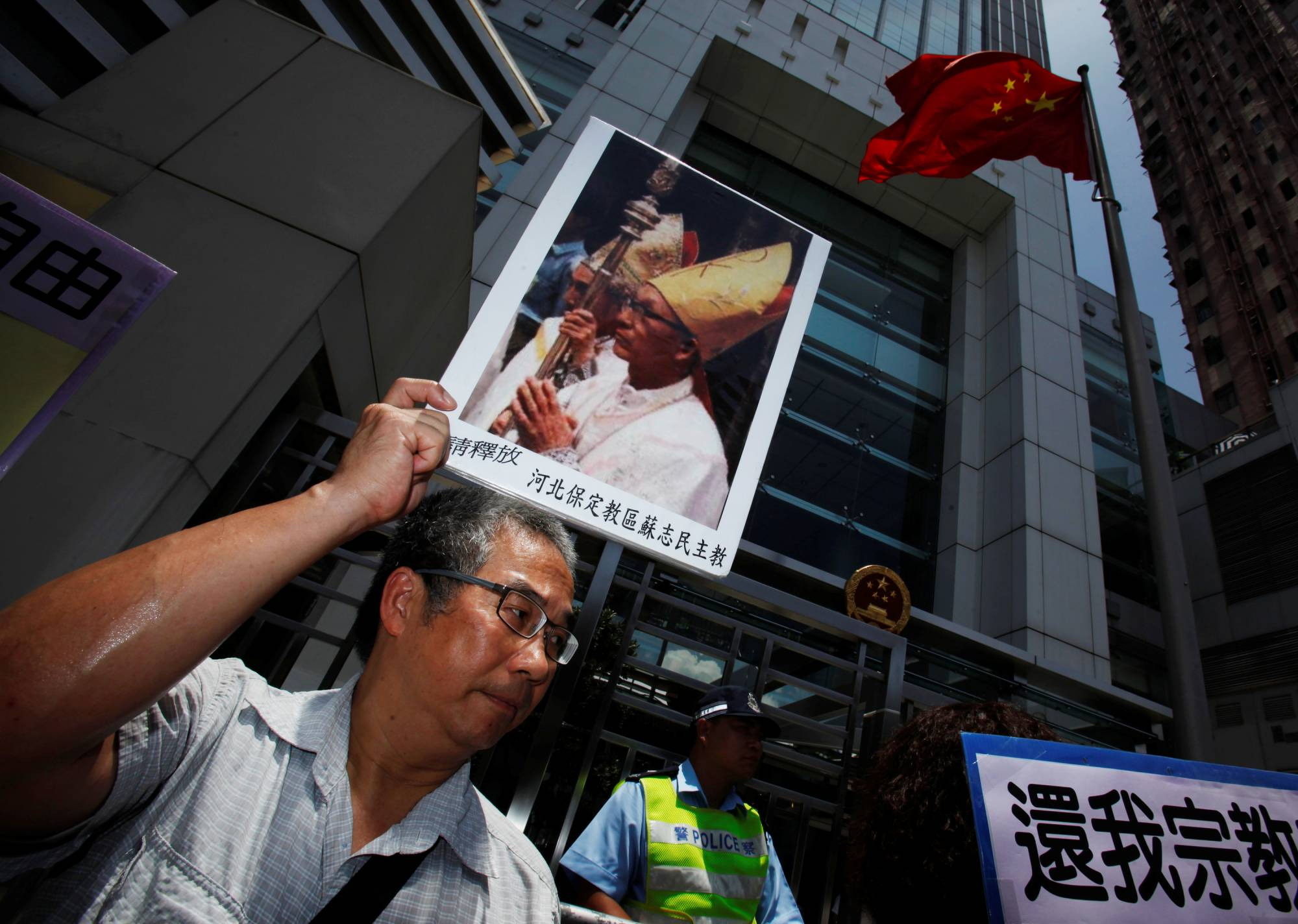 A protester carries a portrait of Bishop Su Zhimin of Baoding in China's Hebei province, in Hong Kong in 2012. The bishop was imprisoned in China and is now unreachable. | REUTERS