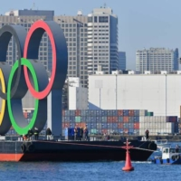 A tugboat tows the Olympic rings upriver Tuesday from a factory in Yokohama where the structure was built.  | RYUSEI TAKAHASHI