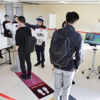 Security checks for next year's Tokyo Olympics and Paralympics are demonstrated to the media in the capital on Oct. 21, with security guards wearing face shields and a thermography device measuring a participant's temperature.  | KYODO