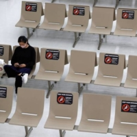 Signs requesting social distancing are displayed on seats in the arrival zone of Narita International Airport, where there are fewer passengers than usual amid the COVID-19 pandemic, in Chiba Prefecture on Nov. 2. | REUTERS
