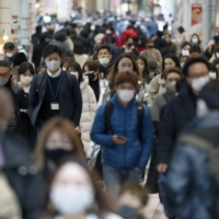 People walk in the city of Osaka's crowded Minami shopping district Wednesday afternoon. Osaka Prefecture reported a record 560 new COVID-19 cases the same day. | KYODO