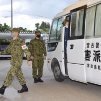 Ground Self-Defense Force members arrive at a care facility for the elderly in the coronavirus-hit city of Miyakojima, Okinawa Prefecture, on Sunday. | KYODO