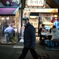 A man wearing a face shield pulls a suitcase along a street in Tokyo on Friday. | AFP-JIJI