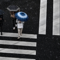 People use umbrellas to shield themselves from the rain and snow while crossing a street in Tokyo on Thursday. | AFP-JIJI