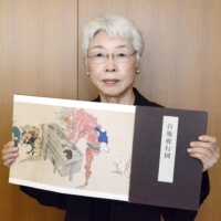 Misako Nagura studied a picture scroll depicting the 'Night Parade of A Hundred Demons,' which shows numerous apparitions and creatures from folklore.