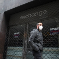 A man walks past a closed currency exchange shop in Buenos Aires on May 22. | REUTERS
