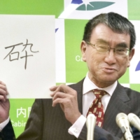 Taro Kono, the minister in charge of administrative reform, shows the kanji character 'sai' (smash) as his kanji of the year to the press on Dec.15. | KYODO