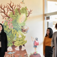 Teresa Currea (left), Oriana Marin (center) and Clara Campos (right) pose in front of a painting that represents the concept of Mother Nature and friendship. | TOMOHIRO OSAKI