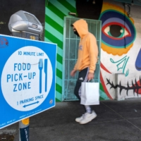 A person walks past a food pick-up zone in Los Angeles on Dec. 8. | AFP-JIJI