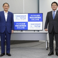 Prime Minister Yoshihide Suga (left) and digital reform minister Takuya Hirai launched an office established by the Cabinet Office and tasked with creating a digital agency, on Sept. 30. | POOL / VIA KYODO